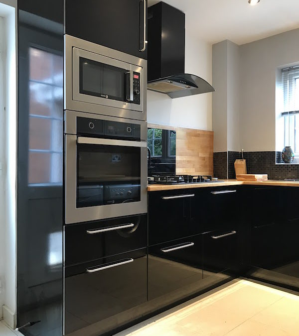 Black high gloss kitchen with slimline pantry.
